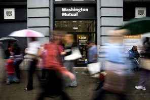 Pedestrians pass a WaMu branch in New York on Sept. 26, 2008, the morning after federal regulators seized the bank.