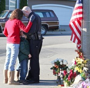 A Puyallup police officer and his family grieve at a memorial outside the Puyallup home of slain Lakewood Sgt. Mark Renninger.