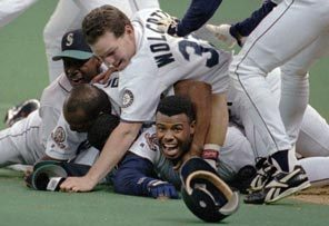 In one of the most recognized moments in Mariners history, Ken Griffey Jr. smiles from beneath a pile of teammates who mobbed him after he scored the winning run in the bottom of the 11th inning against New York Yankees at the Kingdome. The victory advanced Seattle to its first AL Championship Series.