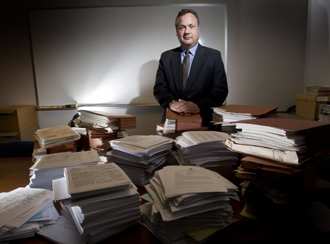 David Hackett, King County prosecutor in charge of civil commitment, stands behind piles of paperwork that represent just slightly more than two cases.