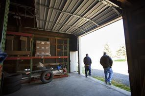 Mike Adams, left, and Keith Bare stand in the doorway of the warehouse annex at McFarland & Co. in Jefferson, N.C. The converted barn is used mainly for storage.