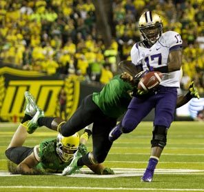 Washington quarterback Keith Price fumbles the ball out of bounds after getting hit yet again by Oregon's quick and forceful defense.