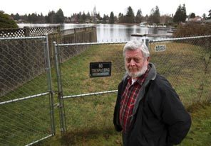 Lee Moyer seen in front of Lake Burien, which is a public lake completely surrounded by private homes. Moyer's efforts to establish a small park at the lake drew a strong negative reaction from homeowners.