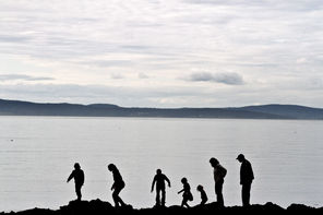 The Nichols family, from Arlington, walks along the rocks on West Beach at Deception Pass State Park.
