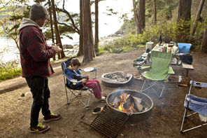 Daniel Braun and his son Oliver Braun, of Seattle, stay warm by the fire at their favorite campsite with a view of the water at Bowman Bay Campground.