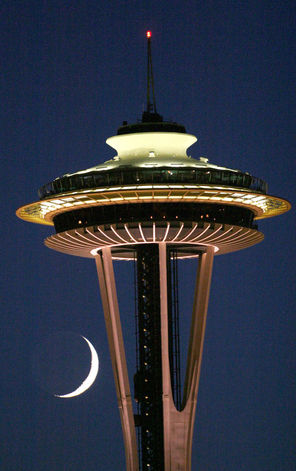 A crescent moon hangs just beneath the observation deck of the Space Needle as twilight fades to night.