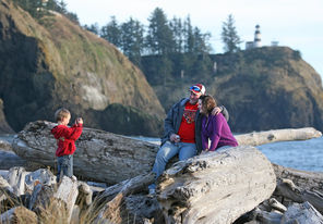 Amanda and Sean Fox, of Rainier, Ore.,  pose as their son, Austin, 4, takes their photo at the edge of the park's Waikiki Beach. Behind them is the Cape Disappointment lighthouse.