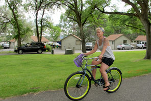 A visitor bikes past lakefront cabins at Sun Lakes Resort, a privately managed part of the state park.