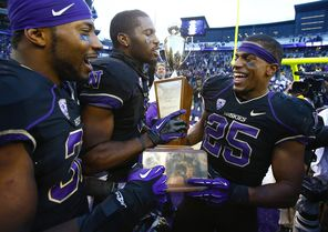 UW's  Bishop Sankey (25) enjoys the Apple Cup trophy along with  Deontae Cooper, far left, and Kevin Smith, center, after beating Washington State 27-17 Friday.