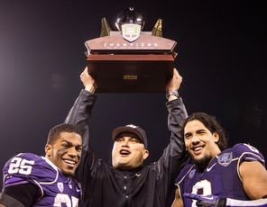 Washington interim head coach Marques Tuiasosopo holds the Fight Hunger Bowl trophy  with offensive and defensive players of the game, Bishop Sankey (25) and Hau'oli Kikaha. <br/>