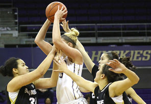 UW's Katie Collier gets a faceful in the midst of  Colorado's  Zoe Beard-Fails, left, Lauren Huggins, top right, and Haley Smith,  bottom right. The Huskies, with a 45-33 rebounding edge,  beat the Buffaloes, 81-71.