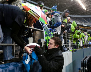 Seahawks general manager John Schneider keeps a low profile, but takes time to sign  autographs for fans.