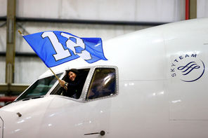 A crew member on a chartered Delta Boeing 767-300 carrying the Seattle Seahawks waves the 12th Man flag as the jet heads   into a hangar Sunday evening at Newark Liberty International Airport, the first stop in a long week of activities before next Sunday's Super Bowl.