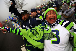 "Marcia Shiri-Wasto cheers with other fans in SeaTac as the Seahawks buses near the airport Sunday morning. ""We're going to win the game for sure,"" she said."