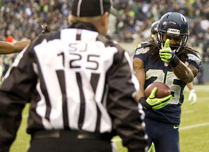 Seattle Seahawks cornerback Richard Sherman doesn't much mind the flag thrown on him — even giving the official him a thumbs up — following his interception against Arizona.