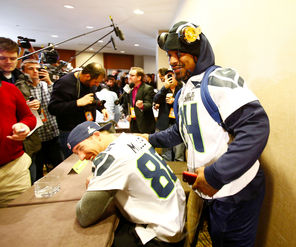 Seahawks running back Marshawn Lynch, right, scoots by teammate Zach Miller to leave a media availability session early.