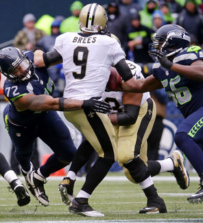 Seahawks defensive ends Michael Bennett, left, and Cliff Avril, right, put the pressure on Drew Brees during their playoff showdown.