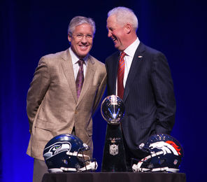 Seahawks coach Pete Carroll, left, and Denver coach John Fox share the stage with the Lombardi Trophy on Friday.