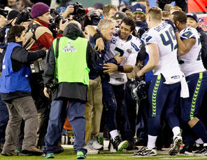 Seahawks  coach Pete Carroll gets an embrace from quarterback Russell Wilson (3) after the final seconds elapsed in Seattle's 43-8 Super Bowl win over the Broncos.