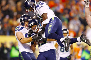 Jermaine Kearse (15) celebrates with  Zach Miller, left,  and   Derrick Coleman, top, after his TD catch.<br/>