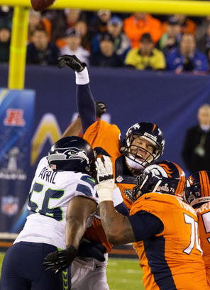 Broncos quarterback Peyton Manning is hit by Seahawks defensive end Cliff Avril as Manning is intercepted by Seahawks linebacker Malcolm Smith, who returned the ball 69 yards for a touchdown.