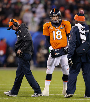 Broncos coach John Fox, left, walks off after talking to Denver quarterback Peyton Manning as the Broncos were totally frustrated in getting anything going offensively in the first half.