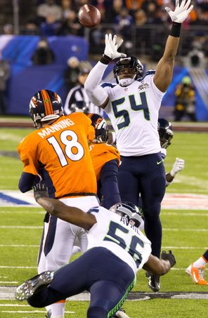 Broncos quarterback Peyton Manning (18) was pressured from the front and the back during the Super Bowl and is shown here lifting a pass over Seahawks linebacker Bobby Wagner (54) in the first half, when Seattle's defense shut out the high-scoring Denver offense.
