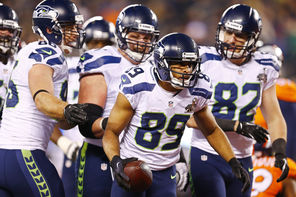 Seahawks players gather around wide receiver Doug Baldwin (89) after Baldwin scores  on a 10-yard touchdown on a  pass from Russell Wilson during the fourth quarter.<br/>