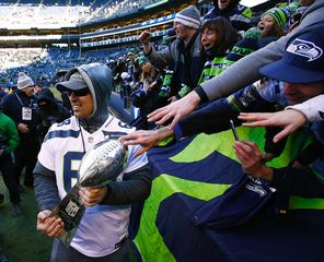 Fans stretch to touch the Lombardi Trophy trotted around by Seahawks player Breno Giacomini.