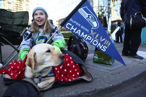 Kaitlyn Steffy, 10, of Woodinville, Wash., sits with the family dog Tina waiting for the Super Bowl champions parade to begin Wednesday.