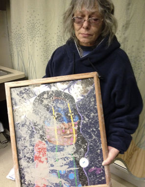 Slide survivor Robin Youngblood with a muddy picture from her destroyed home.
