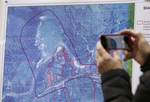 A journalist photographs a map showing the location of Saturday's deadly mudslide near Oso, Snohomish County. Officials in a Monday news conference said the Stillaguamish River  flooded several buildings upstream from the slide, but that the river had begun cutting a new channel and water levels were starting to subside.