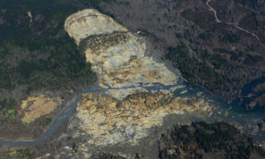 An aerial photo taken Monday shows the massive mudslide east of Arlington that killed at least 14 people and left dozens missing. Experts who have studied the hillside over the years have warned of slide danger, but county officials say the disaster came as a surprise.