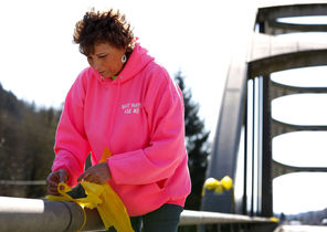 "Debra Hoskins, a church pastor, ties yellow ribbons Tuesday onto a bridge crossing the North Fork of the Stillaguamish River, down the road from the   slide. ""Ribbons signify that you expect the return of a loved one,"" she said."