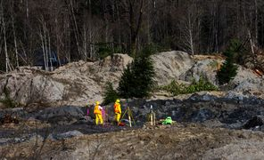 Workers with surveying equipment work in the mudslide debris field west of Darrington on Wednesday.