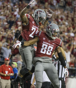 Washington State's Theron West jumps onto the back of Isiah Myers after Myers caught a touchdown pass in the Cougars' season-opening loss.