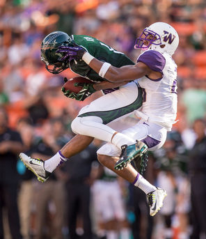 Hawaii's Marcus Kemp pulls down a tipped pass, defended by Washington's Marcus Peters. The reception got Hawaii into the red zone from where they would score a field goal in the first quarter.